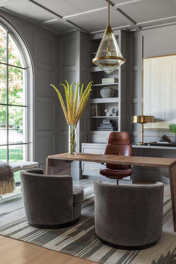 un bureau à domicile gris super élégant avec des murs lambrissés gris, un bureau accrocheur, des chaises grises et des étagères intégrées ainsi qu'une fenêtre cintrée