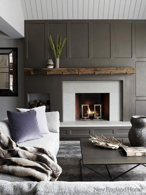 un salon moderne et accueillant avec un mur de panneaux gris et une cheminée qui se démarque beaucoup