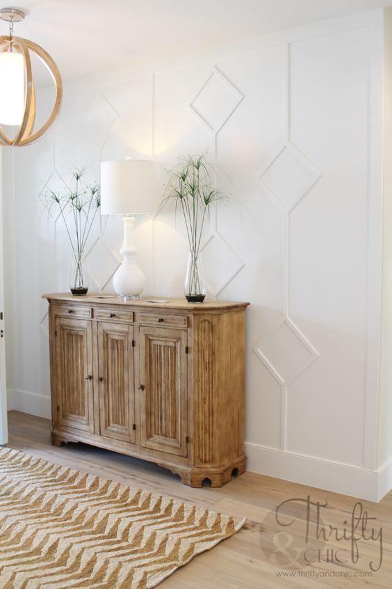 une élégante entrée de ferme avec un mur lambrissé blanc, un buffet et un lustre en bois, une lampe blanche et de la verdure