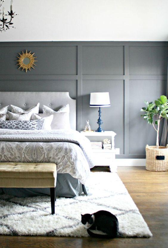 une chambre aérée avec un mur lambrissé gris clair, des meubles rembourrés, des textiles imprimés et des tapis ainsi que des lampes audacieuses chics