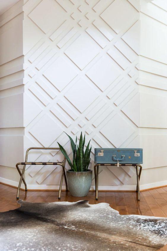 une entrée ultra-moderne avec des murs lambrissés blancs qui semblent accrocheurs, ajoutent du motif et de la texture à l'espace