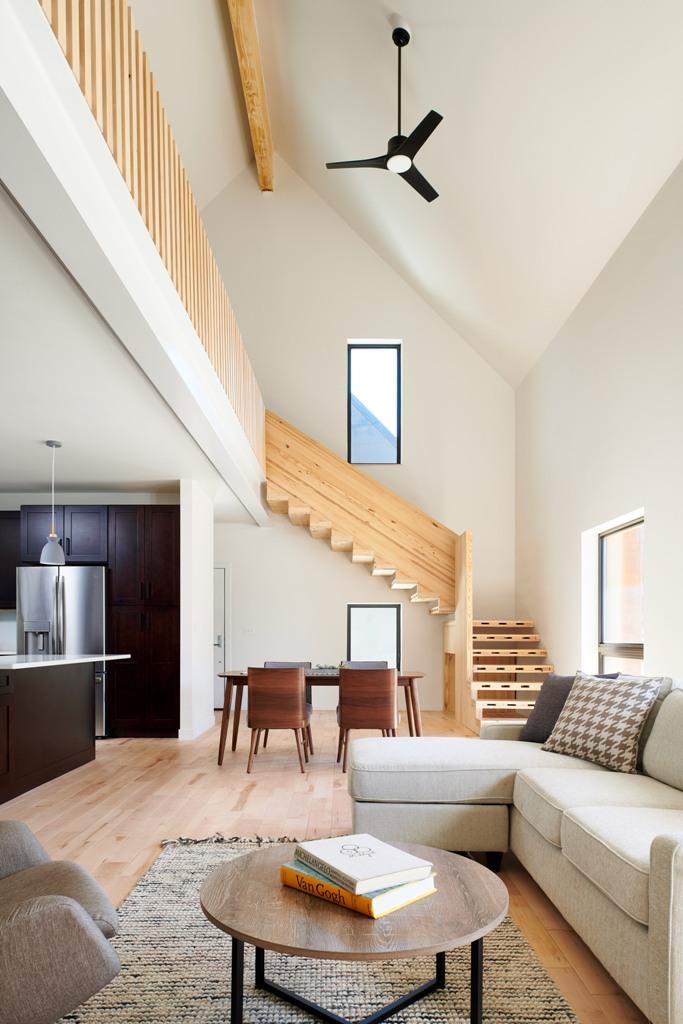 L'espace principal est un aménagement ouvert avec une cuisine, un espace salle à manger et un salon plus un grand escalier en bois qui mène au deuxième étage