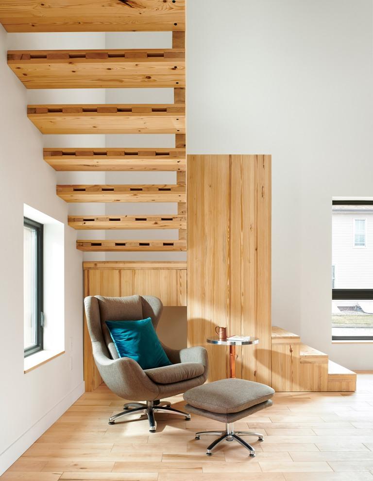 L'espace sous les escaliers a été occupé par un coin lecture confortable avec une chaise confortable et un repose-pieds