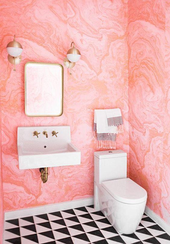 une salle d'eau audacieuse avec du papier peint aquarelle rose sur les murs, des carreaux noirs et blancs et des luminaires en laiton pour plus de chic