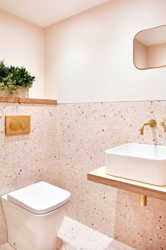 une salle d'eau blush avec des carreaux de terrazzo et de la peinture, une vanité flottante et des luminaires en or et des touches ici et là