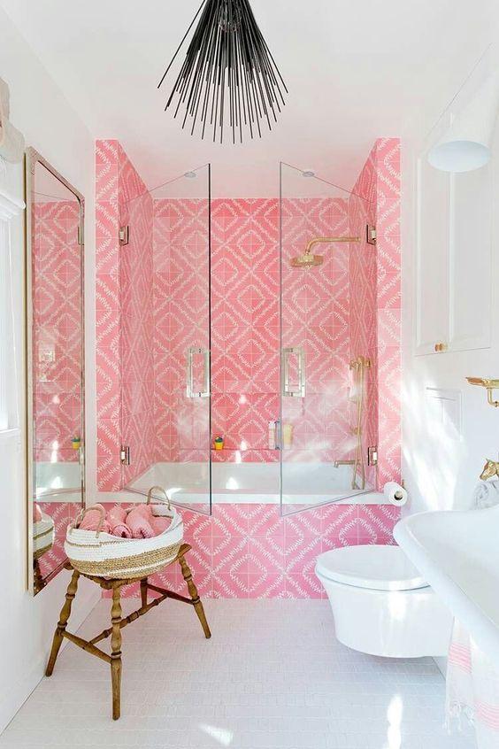une salle de bain contemporaine audacieuse avec un espace baignoire revêtu de carreaux rose vif, des luminaires dorés et un miroir dans un cadre doré