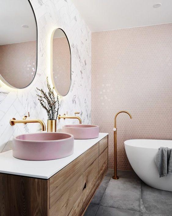 une salle de bain contemporaine avec des carreaux hexagonaux blush sur le mur, des lavabos roses, des luminaires glam et des miroirs à cadre doré éclairés