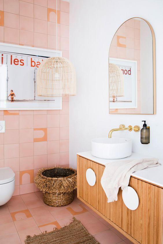 une salle de bain accrocheuse avec des carreaux roses, une lampe et un panier en osier, une vanité flottante et des luminaires dorés pour une touche glamour