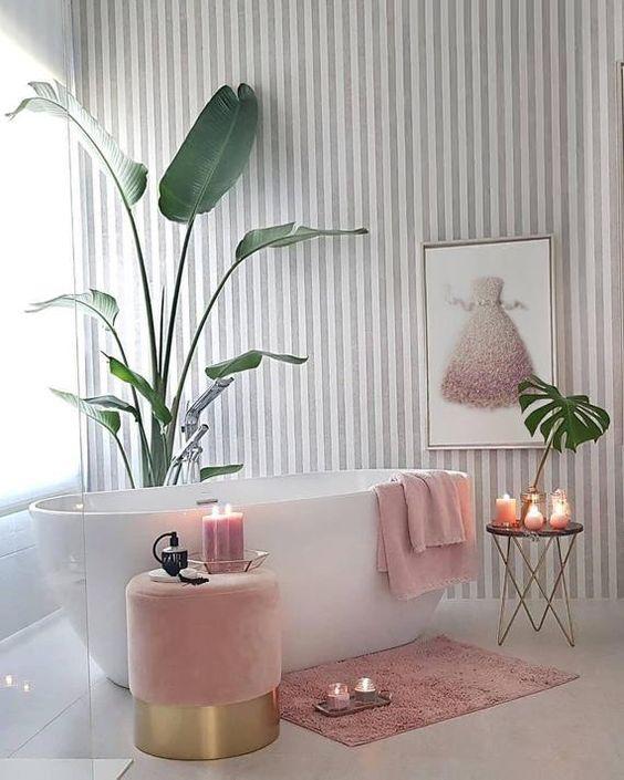 une salle de bains glamour contemporaine avec un mur de papier peint à rayures, une illustration de robe rose, des serviettes roses et un pouf, un tapis rose et des bougies plus des touches d'or