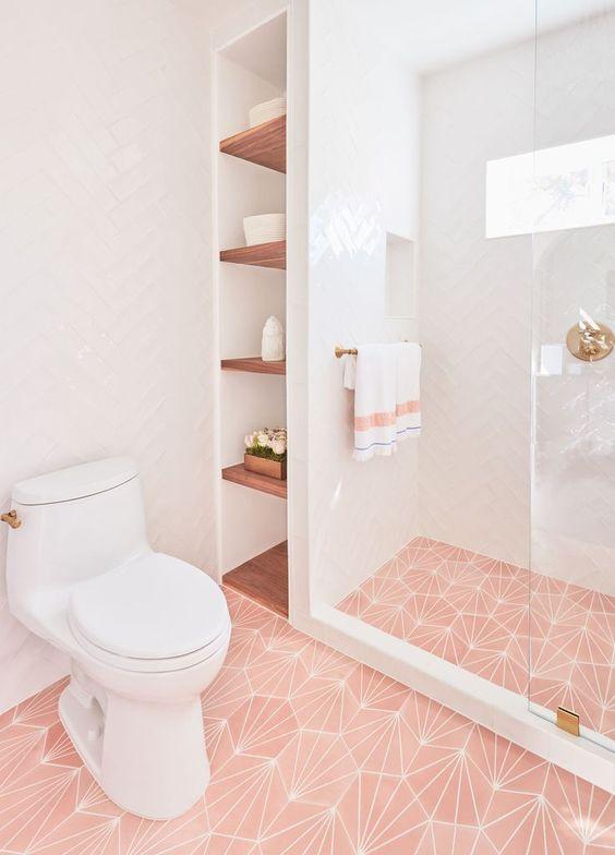 une salle de bains contemporaine chic avec des carreaux imprimés roses au sol, des touches et des accessoires dorés ainsi que de simples carreaux blancs sur les murs