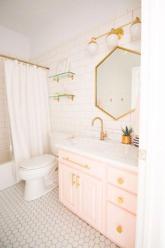 une salle de bain contemporaine revêtue de carreaux blancs, avec une vanité rose clair, des luminaires dorés, des boutons et un miroir géométrique