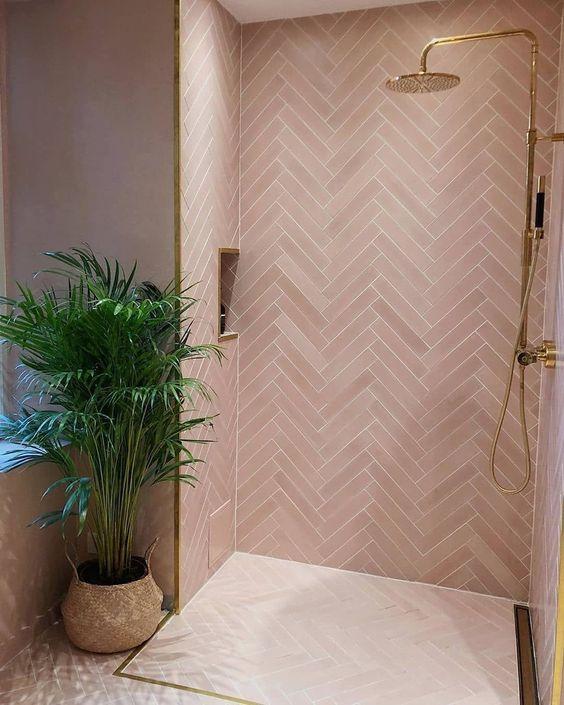 une salle de bain rose contemporaine revêtue de carreaux roses dans un motif à chevrons, des luminaires et des cadres dorés pour un look glamour