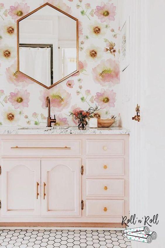 une salle de bain chic et fille avec du papier peint à fleurs rose, une vanité rose clair et des luminaires et des cadres en or et en cuivre