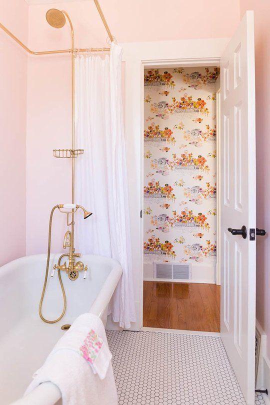 une salle de bain glamour avec des murs rose clair, des luminaires dorés et de jolies serviettes fleuries avec des touches roses