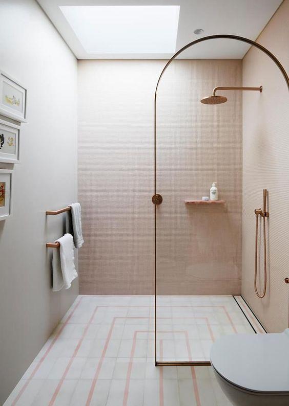 une jolie salle de bain contemporaine avec des carreaux blush sur les murs, un sol carrelé à motifs, des luminaires en laiton et un diviseur de cadre en laiton