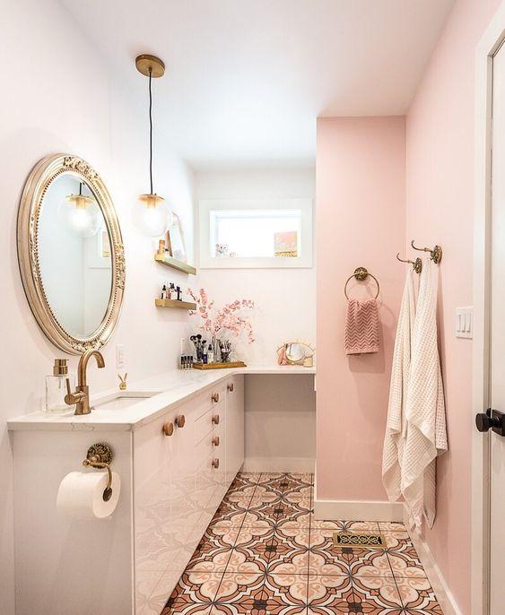 une jolie salle de bain glamour avec des murs roses et blancs, des serviettes roses, des luminaires en laiton et or et un miroir raffiné dans un cadre chic
