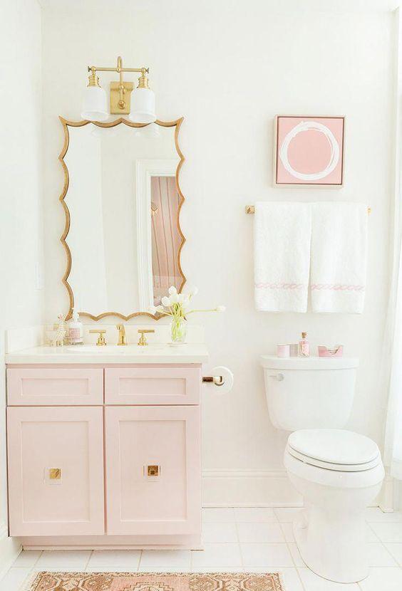 une salle de bains contemporaine glamour avec une vanité rose clair, des œuvres d'art et des accessoires, des luminaires dorés et un miroir accrocheur dans un cadre doré