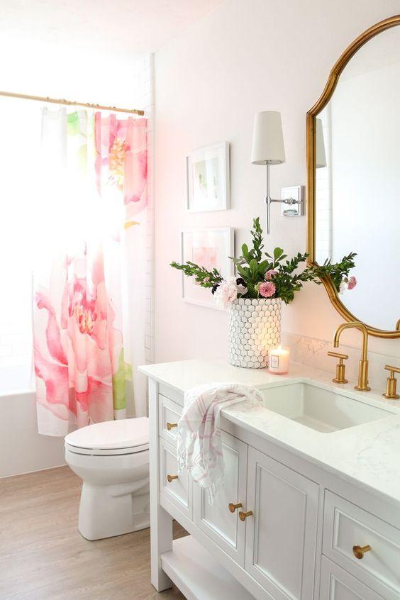 une jolie salle de bains glamour avec des murs ombrés blush, un rideau de fleurs roses, des luminaires dorés et un miroir chic à cadre doré et des fleurs roses