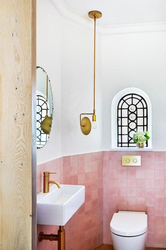 une salle d'eau petite mais audacieuse revêtue de carreaux roses, avec des luminaires en or et une suspension accrocheuse a l'air wow