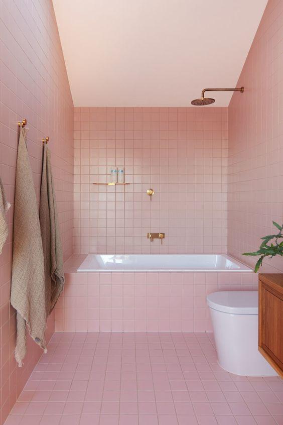 une salle de bain glamour moderne revêtue de carreaux roses et finie avec des luminaires en laiton et or pour un look chic