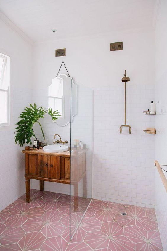 une petite salle de bain contemporaine avec un sol en carrelage rose et des touches et des luminaires en laiton et rose pour un look audacieux