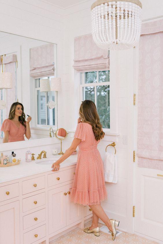 une salle de bain rose d'inspiration vintage glam avec des nuances roses, des carreaux roses au sol, une vanité blush et des touches d'or ici et là