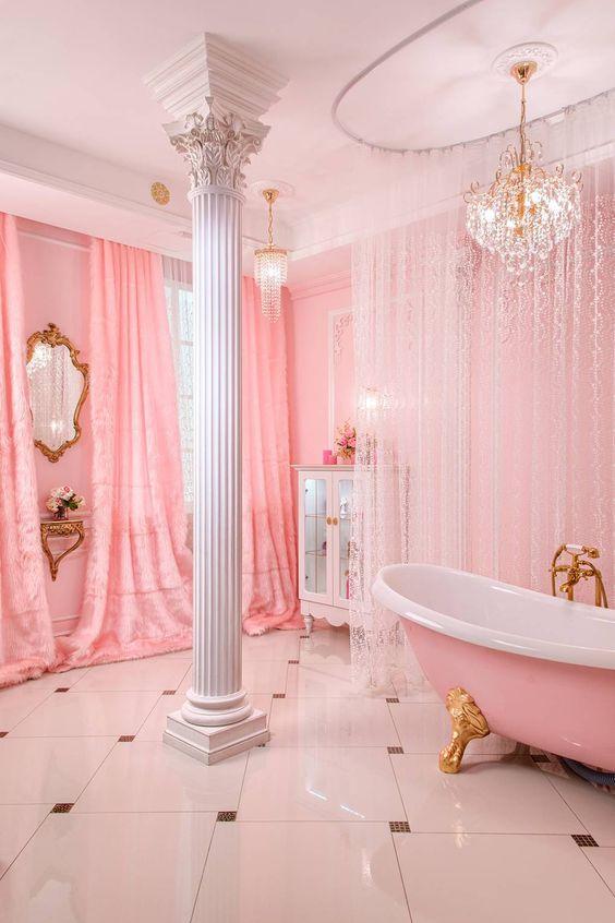 une salle de bain rose raffinée et glamour avec des rideaux et des rideaux de dentelle, une baignoire rose sur pieds dorés, un lustre en cristal glam et un pilier