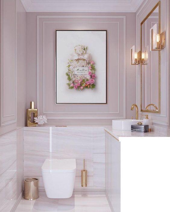 une salle d'eau rose pâle avec des carreaux de marbre blanc et rose, des accessoires dorés et un encadrement pour une touche chic et glamour