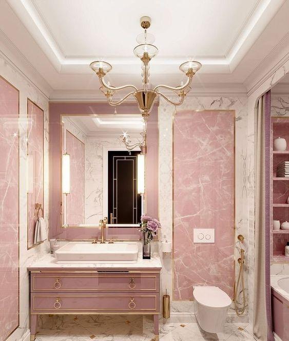 une salle de bain rose glamour faite de pierre et de marbre, avec une vanité rose raffinée, un lustre vintage et des luminaires en or