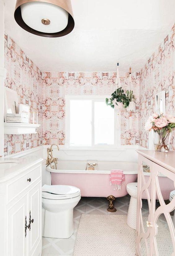 une salle de bains élégante d'inspiration vintage avec du papier peint imprimé rose, une baignoire rose, un buffet rose et des fixations et des pieds en laiton