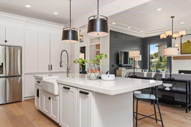 La cuisine est ajustée au salon et est faite en blanc, avec des lampes blakc