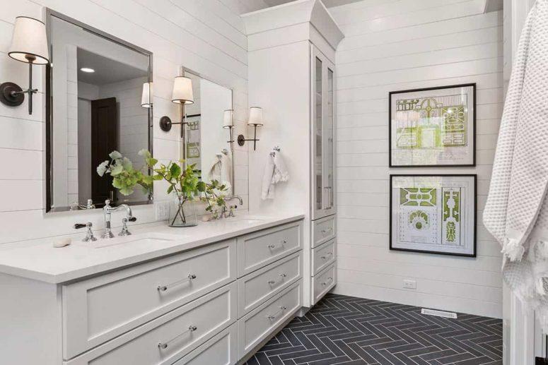 La salle de bain principale est faite de feuillures blanches et d'un sol en carrelage gris