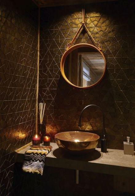 une salle de bain chic noir et or avec des carreaux géométriques, des accents dorés et un miroir à cadre doré plus un lavabo unique