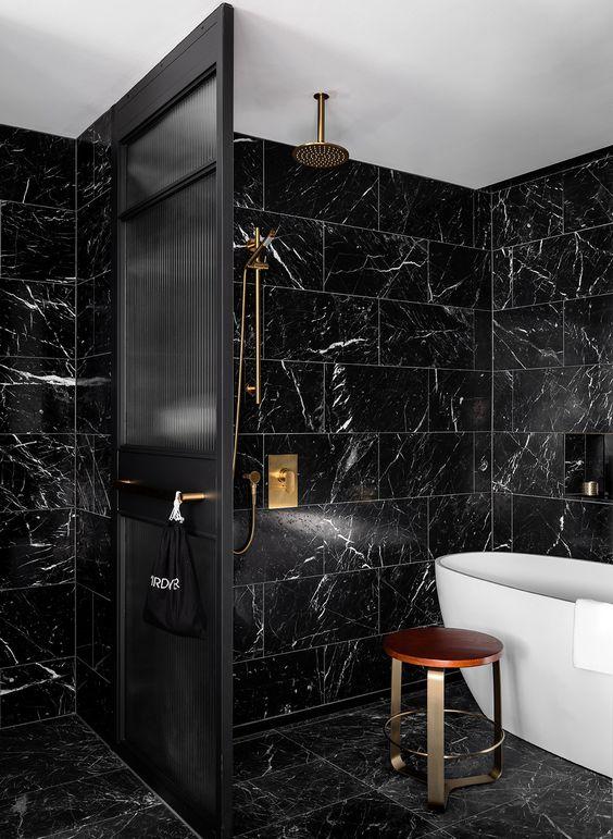 une salle de bain chic noir et or avec des carreaux de marbre noir, des luminaires noirs, un séparateur d'espace noir et une baignoire blanche
