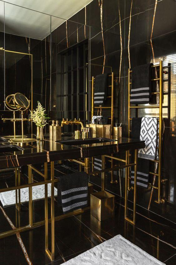 une salle de bain art déco audacieuse en noir et or, avec du marbre, du métal et de nombreuses touches graphiques ici et là et des accessoires en or