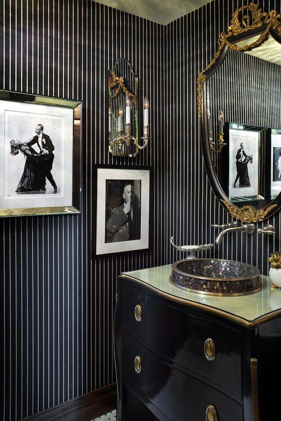 une salle de bain vintage audacieuse noire et or avec une coiffeuse élégante, un lavabo accrocheur, un miroir raffiné et des œuvres d'art audacieuses