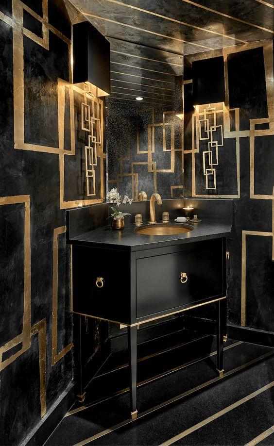 une salle de bains luxueuse en noir et or avec une vanité géométrique, des détails géométriques dorés et des luminaires et des bougies dorés