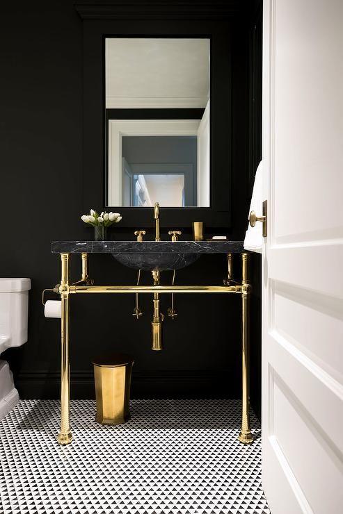 une salle d'eau chic avec des murs noirs, un évier en marbre noir, des luminaires et des pieds dorés ainsi qu'un sol en mosaïque