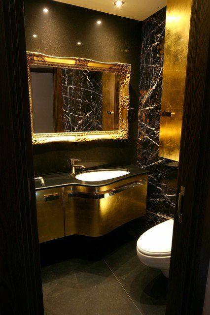une salle d'eau luxueuse avec des murs noirs, des touches dorées chics, une vanité dorée, des lumières intégrées et des appareils blancs
