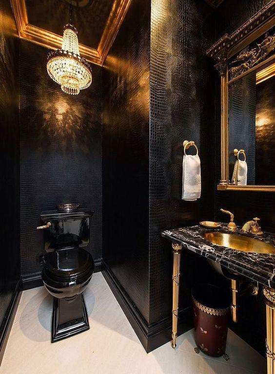 une salle d'eau luxueuse avec des murs en cuir noir, un lustre en cristal, une toilette noire, un meuble-lavabo en marbre noir et un lavabo en or