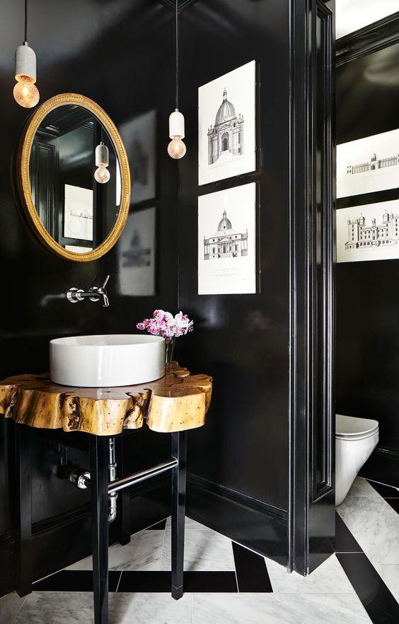 une magnifique salle de bain avec un sol en mosaïque, des murs noirs, un miroir à cadre doré, une vanité en tranches de bois et des œuvres d'art