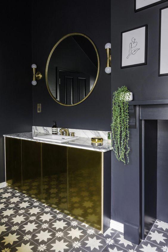 une salle de bain chic noir et or avec des murs noirs mats, une coiffeuse en or poli, des luminaires et des lampes dorés et un sol en mosaïque