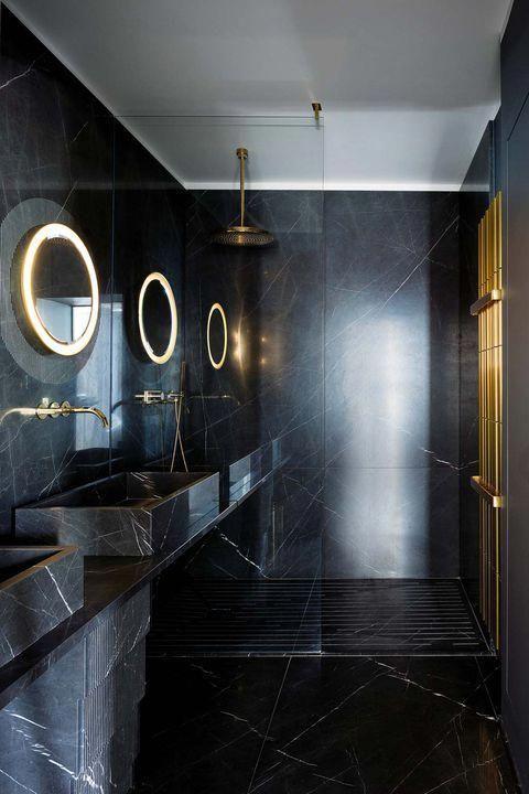 une salle de bain minimaliste noir et or revêtue de marbre noir, avec des miroirs éclairés, des accessoires et des luminaires en or