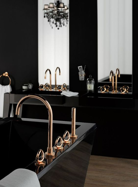 une salle de bain moderne et raffinée avec des lavabos noirs, une baignoire sculpturale noire, un lustre blakc chic, des luminaires dorés et de grands miroirs