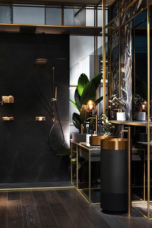 une salle de bains moderne et raffinée en noir et or, avec des éviers et des luminaires en or, avec des lampes accrocheuses et des plantes en pot