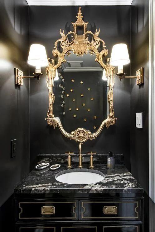 une salle de bain raffinée en noir et or avec un miroir orné chic, des appliques murales, une coiffeuse noire et un lavabo blanc