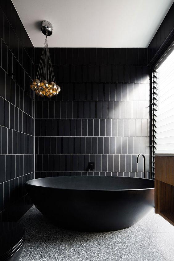 une salle de bain minimaliste noir et or avec un sol en pierre, un lustre à bulles et une jolie baignoire sur pied