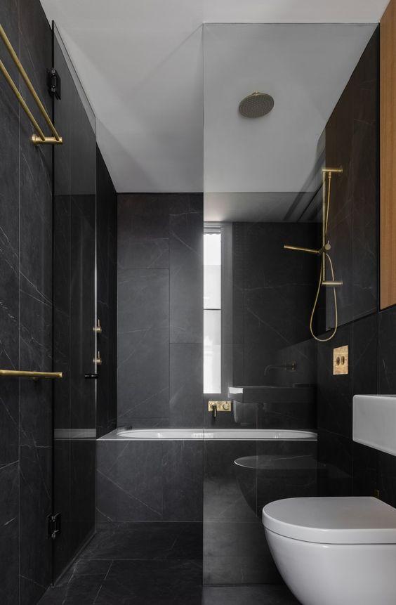 une salle de bain minimaliste noir et or avec des carreaux de marbre noir, des luminaires en or et des appareils blancs est super élégante