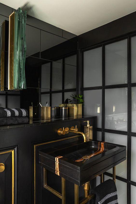 une salle d'eau élégante et luxueuse en noir et or, avec un cadre et des accessoires dorés ainsi qu'un évier en marbre chic