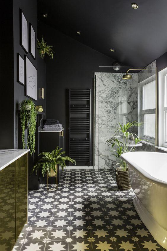une salle de bains moderne et élégante avec des murs noirs mats, une coiffeuse en or, des jardinières et des accessoires dorés ainsi que des carreaux monochromes sympas